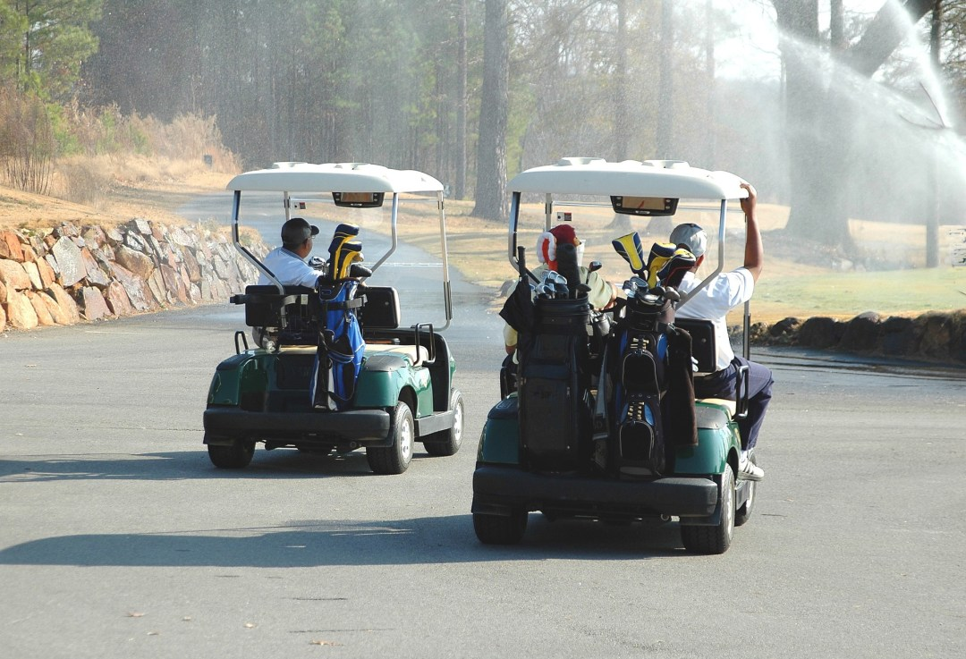 Group of Men is riding a golf cart