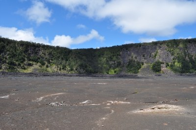 Lush forest surrounds the lava lake bed