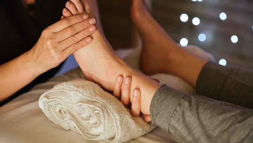 crop therapist massaging foot of client