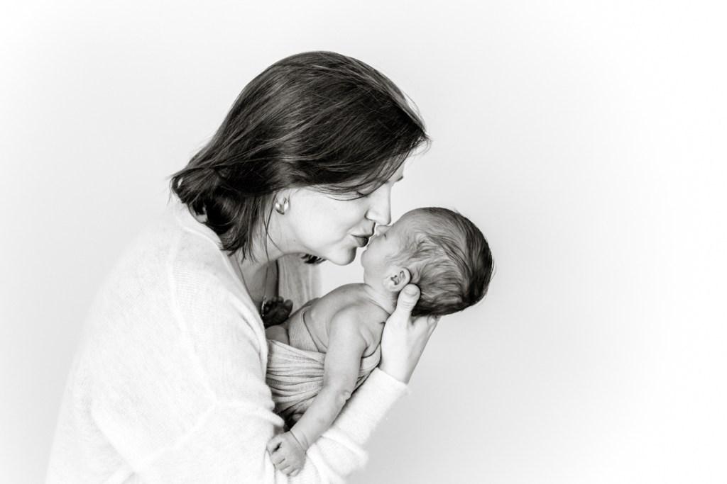 mum kissing newborn on his hands