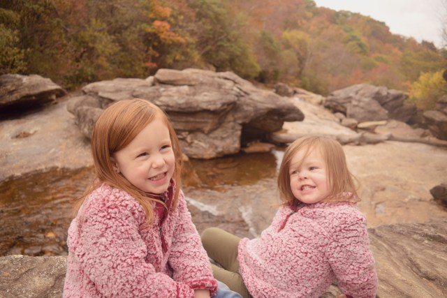 my daughters smiling, sitting in front of the water at graveyard falls.