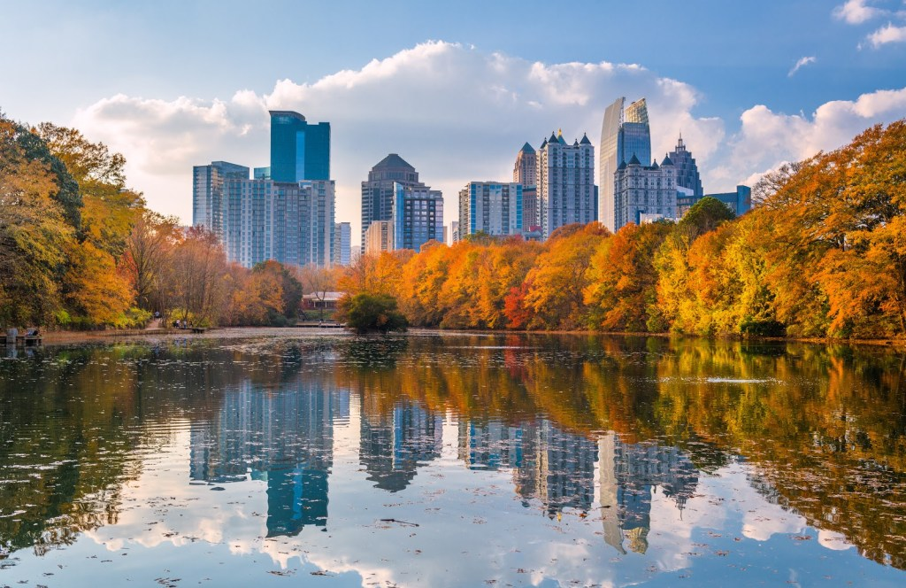 things to do in atlanta with kids, lake view surrounded by fall colored trees and a city scape in the background