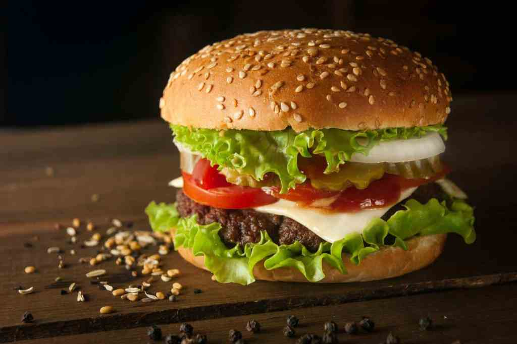 burger with cheese, ketchup, lettuce, onion, tomato, pickle