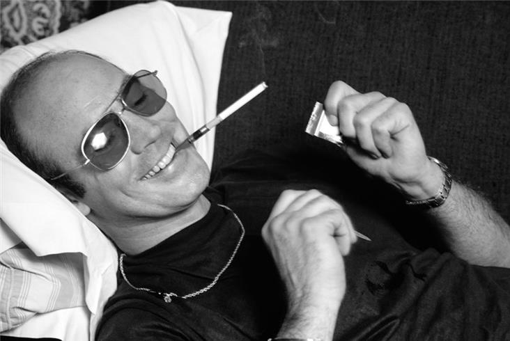 1977 hunter thompson-lying on couch-smoking and smiling-Gramercy Hotel-2-Edit