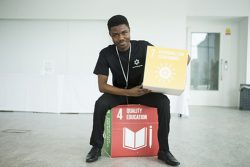 Movement Makers volunteer holding Global Goals for Sustainable Development cubes 4 Quality Education and 7 Affordable and Clean energy