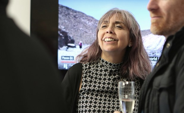 Sandra Codd from Chakana smiling in front of a screen showing the film about the first working group in the Andes