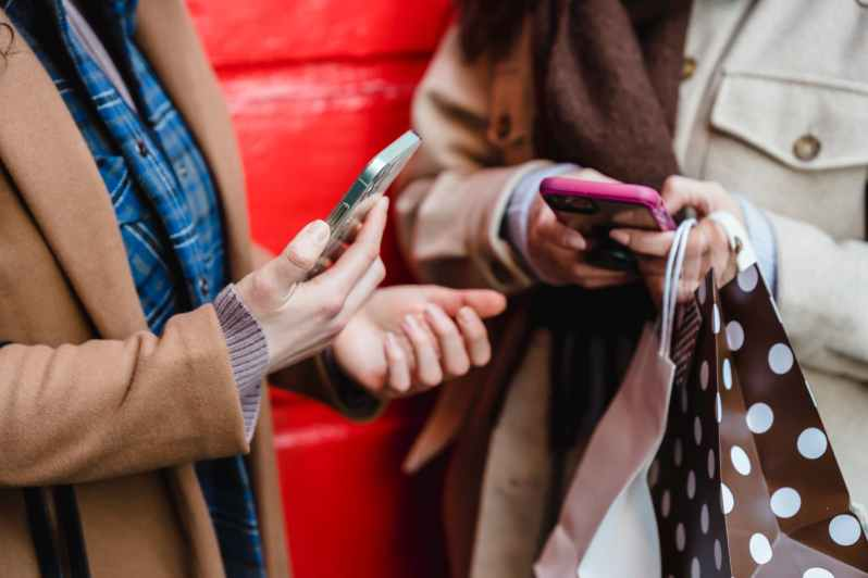 unrecognizable women messaging on smartphones after shopping in city