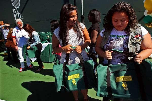 Alma Roque, right, and fellow players marvel at gifts of gear during a Beverly Hills Tennis Club lunch. (Genaro Molina, Los Angeles Times / October 19, 2013)