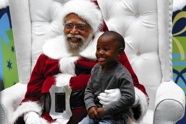 "Jahleel Logan, 3, poses with Santa, a.k.a. Langston Patterson, 77, of Rudolph Holiday Photo, at the Baldwin Hills Crenshaw Plaza, Dec. 7, 2013. Patterson has been Santa at the Plaza since 2004, with African American families coming at specific times of the day, just to visit him. ""I just don't want him to think that all greatness comes from a different race,"" said Logan's godmother, Arlene Graves, 45. ""There are Santa Clauses his color doing good work too."" (Jay L. Clendenin / Los Angeles Times)"