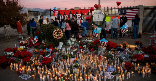People gather at a makeshift memorial near the Inland Regional Center during the aftermath of a mass shooting that killed 14 people on Sunday, December 6, 2015 in San Bernardino, California, USA. AFP PHOTO/PATRICK T. FALLON / AFP / Patrick T. Fallon        (Photo credit should read PATRICK T. FALLON/AFP/Getty Images)