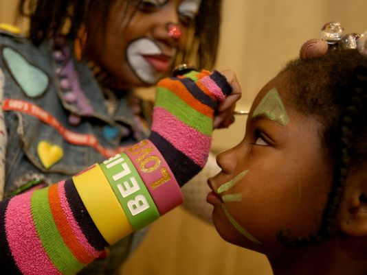 (L to R) Dawn Wilson-Clark of Detroit who plays Kuddles the Clown works at painting the face of Ramiyah Johnson, 5 of Detroit on Saturday, Dec. 5, 2015. (Photo: Eric Seals Detroit Free Press)
