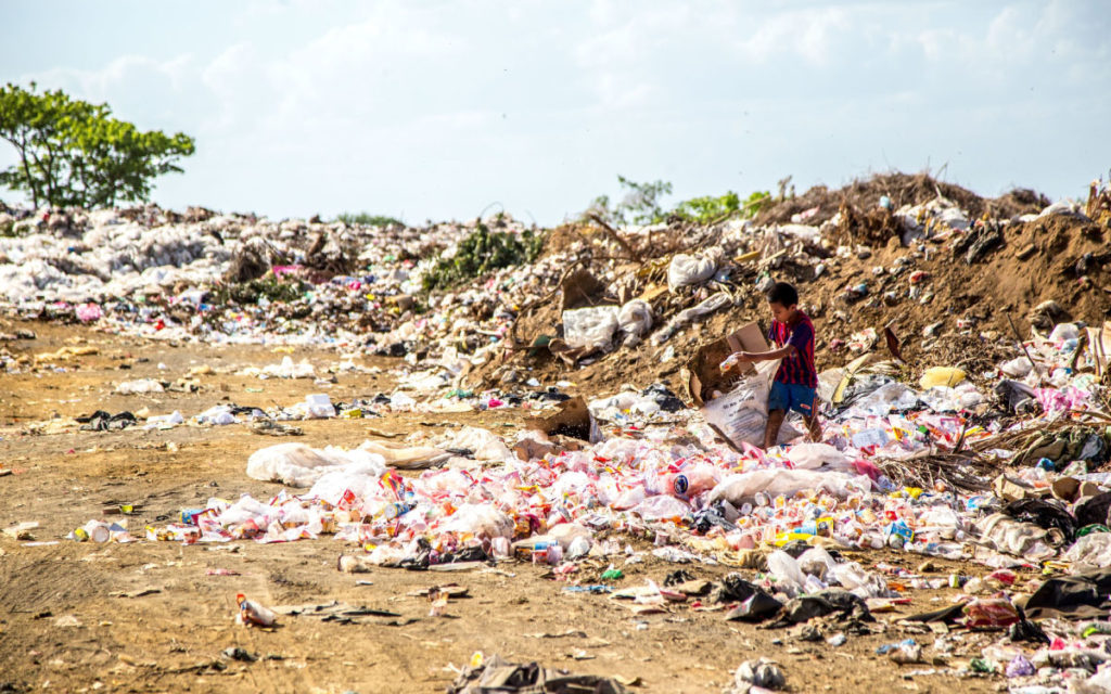 boy collecting trash at Asian landfill