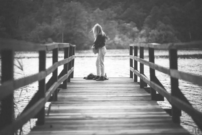 kaboompics-com_alone-girl-standing-on-the-wooden-pier