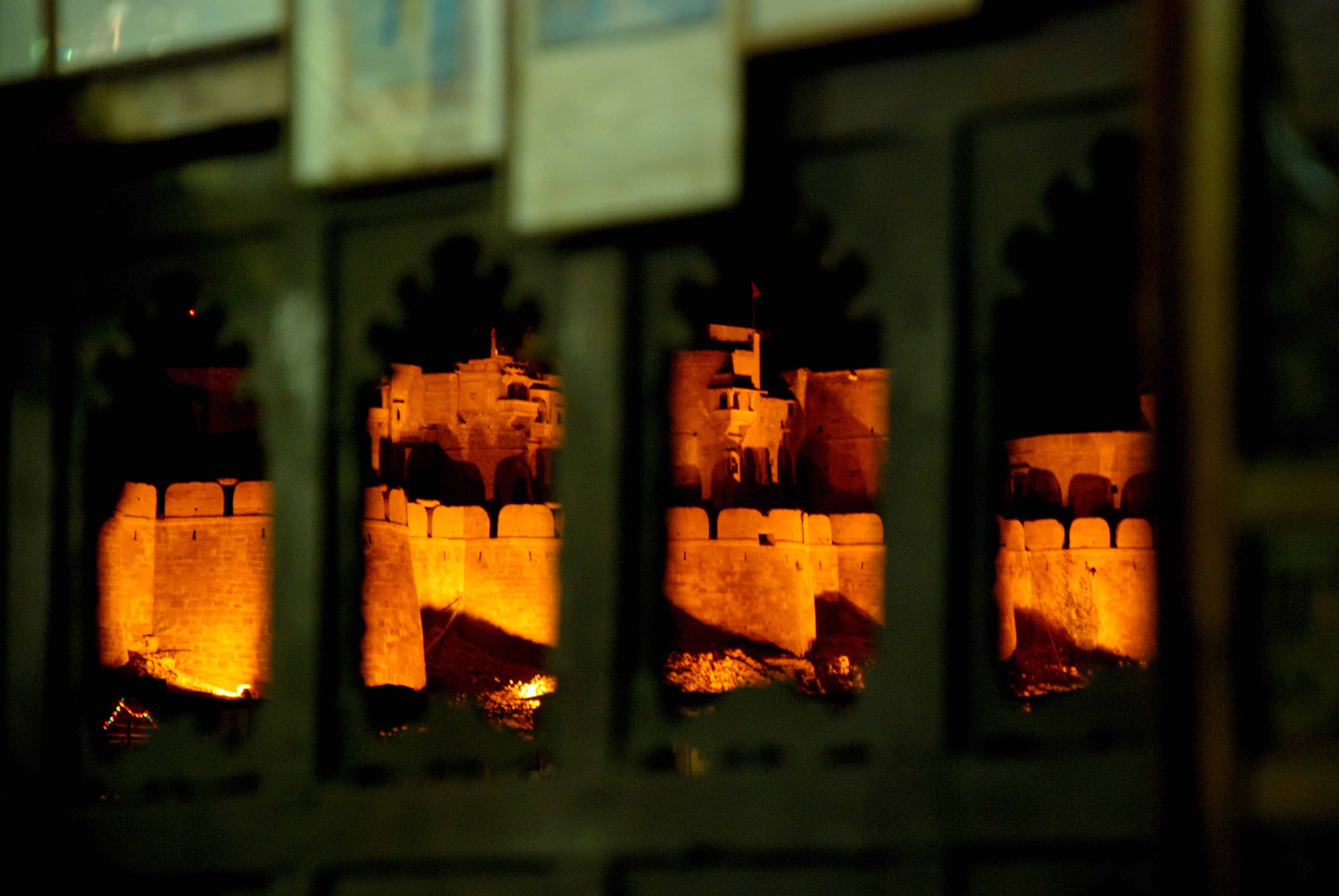 The illuminated fort viewed through the window panels of a restaurant.