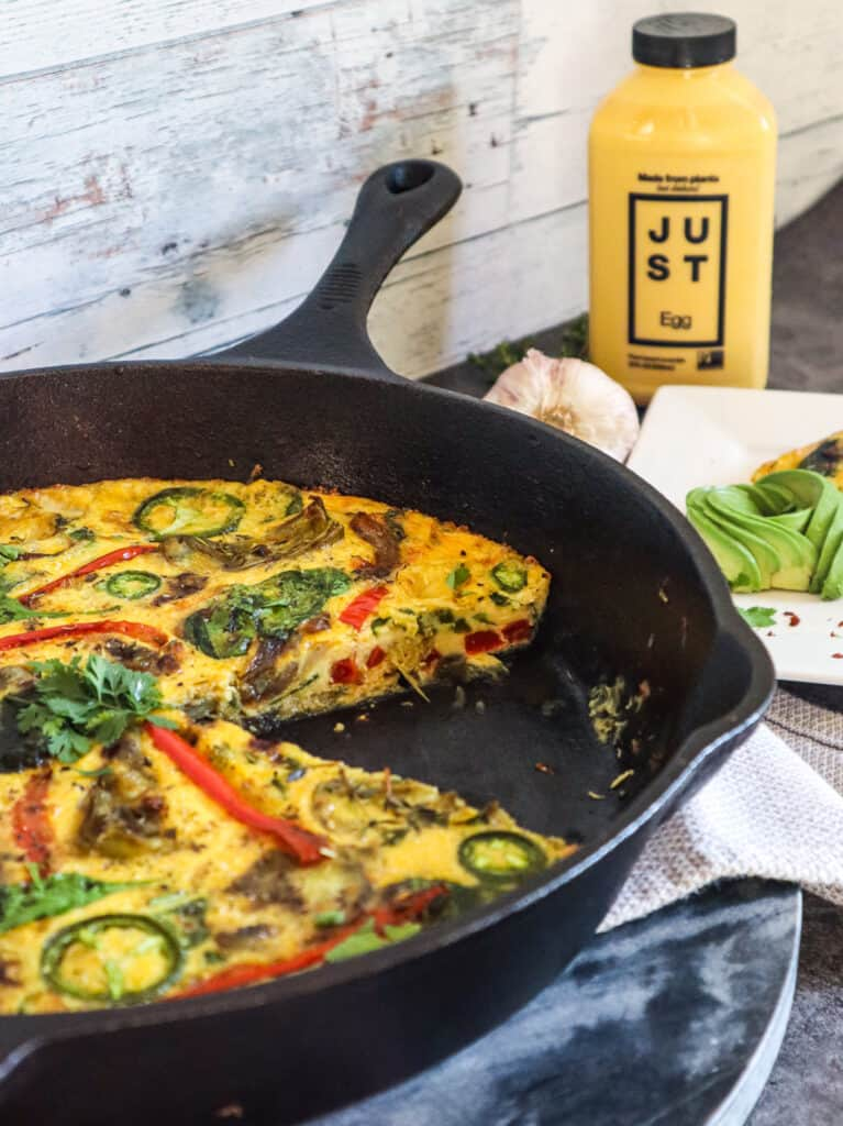 Vegan eggless frittata using JUST Egg pictured in cast iron with JUST EGG product in background