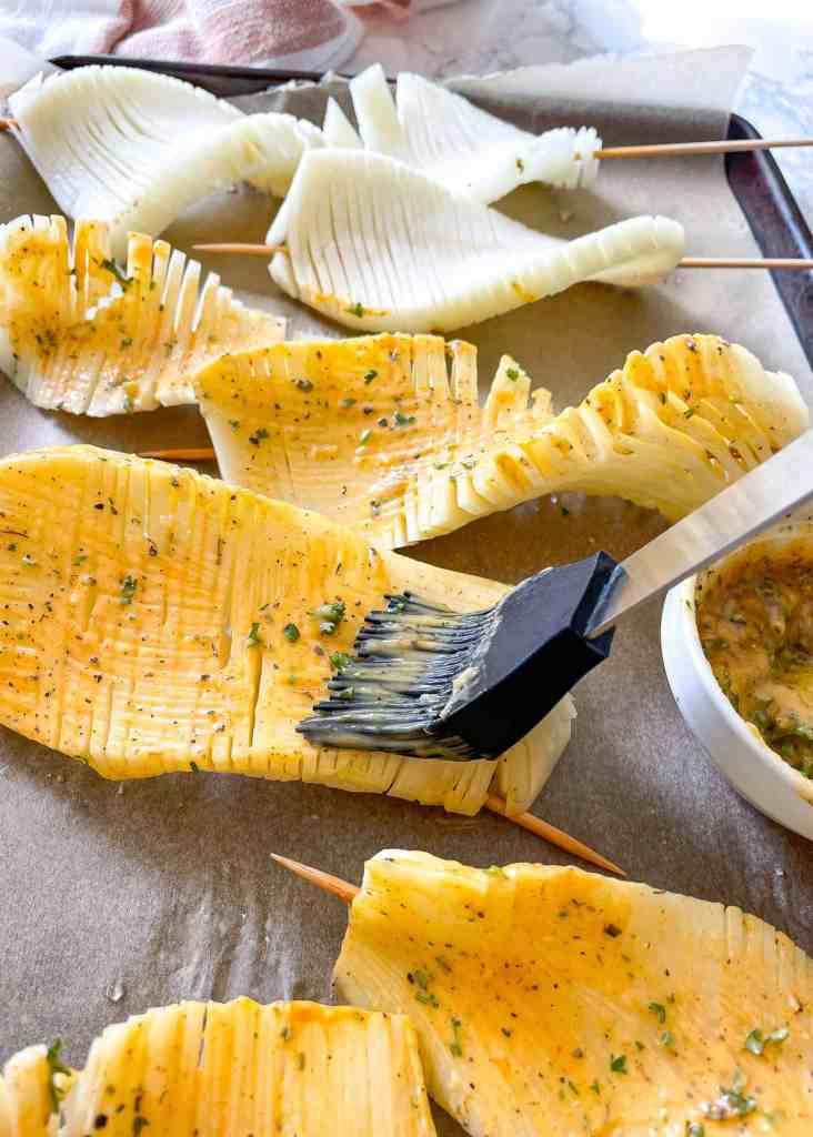 image of a brush putting garlic herb butter on an accordion potato skewer