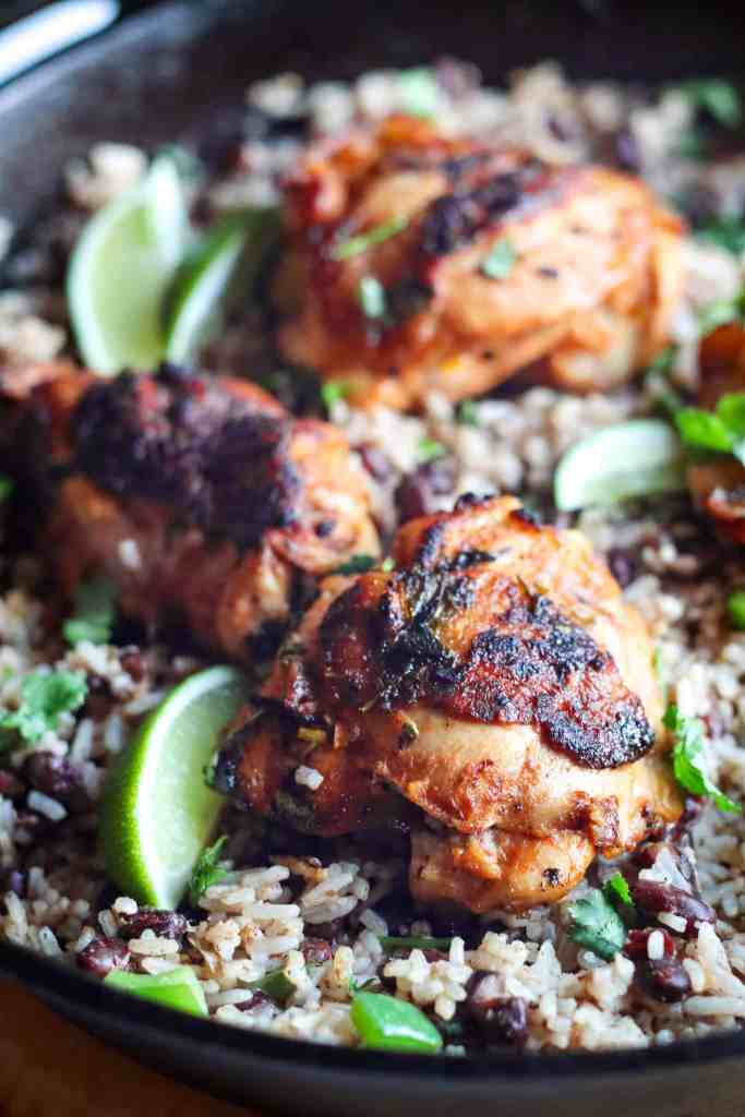 close up image of cilantro lime chicken thighs over rice and beans in a cast iron skillet