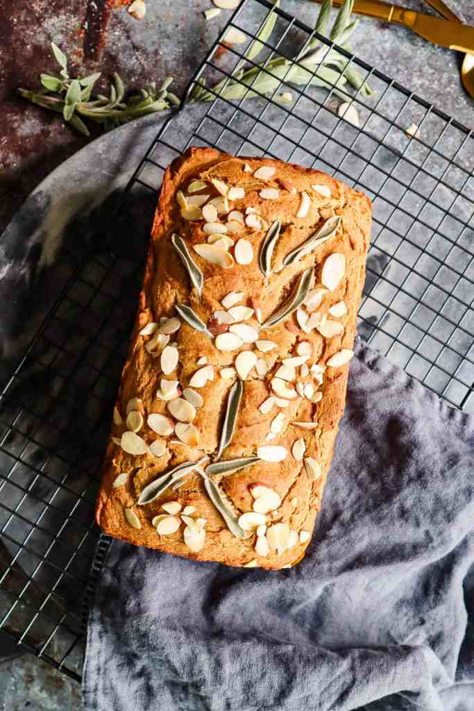 flat-lay image of Gluten Free Sweet Potato Bread placed on a wire rack with fresh sage sprig in background