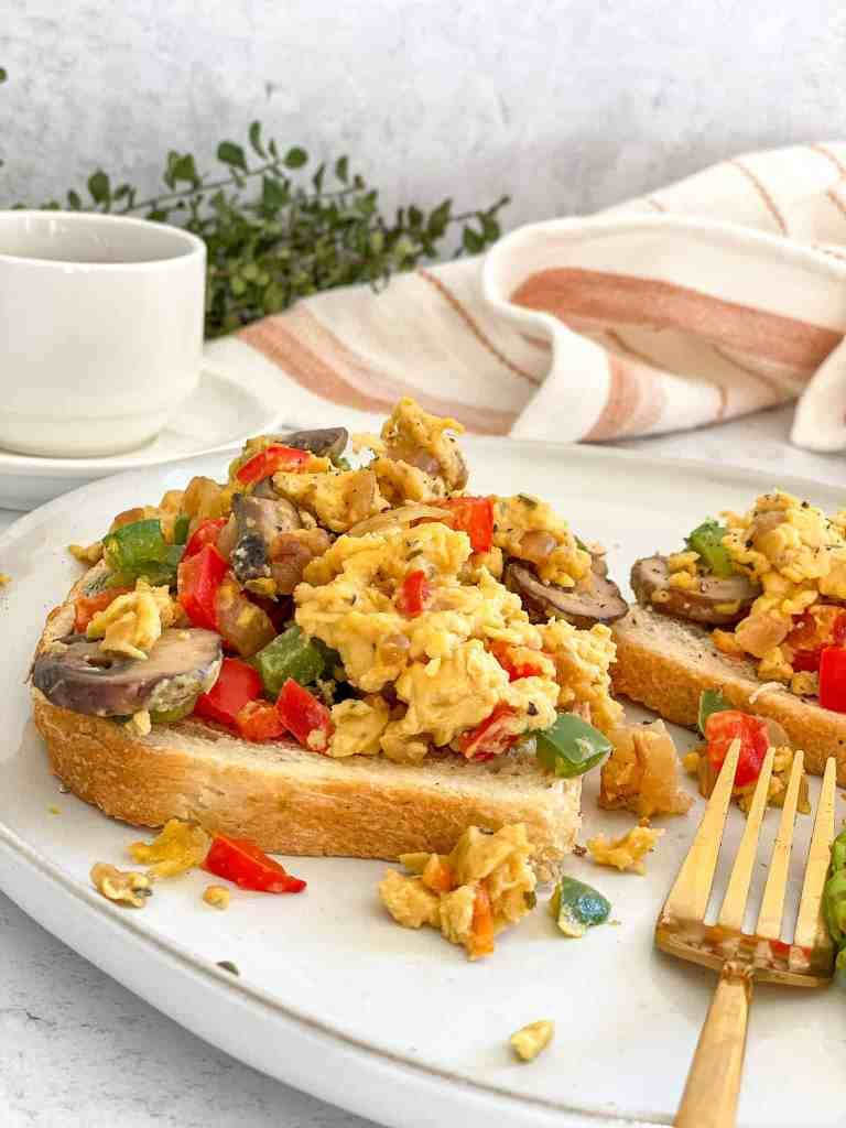Fluffy Vegan Egg Scramble with peppers, mushooms, adn onons served over toast
