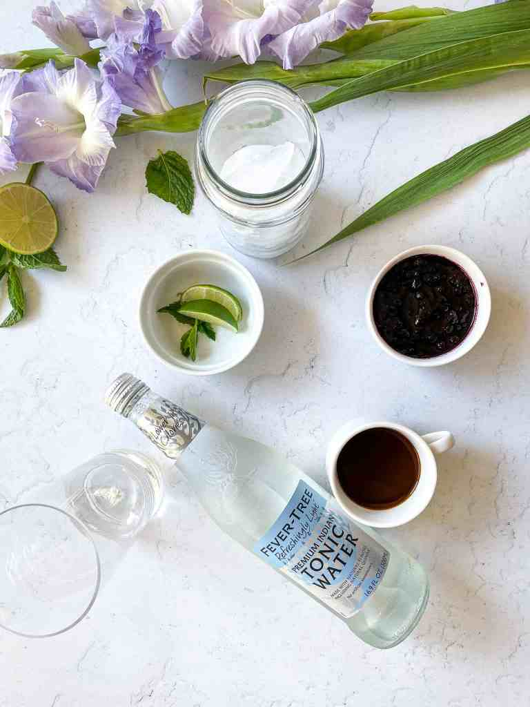 Ingredients needed to make blueberry espresso tonic. Fever tree tonic water, double shot of espresso, blueberry simple syrup, lime, mint, ice