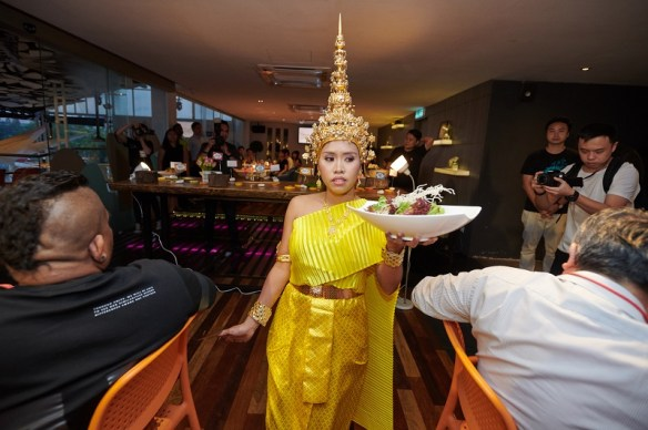 A server in Thai costume serving Sawadee Salad