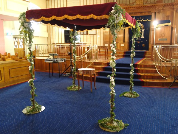 Chuppah decorated with eucalyptus leaves, golden rod, Queen Anne's lace and chrysanthemums