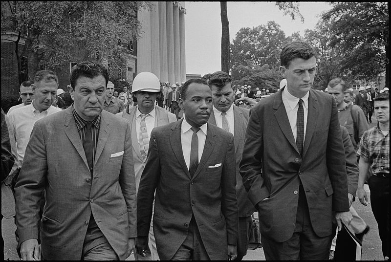 James Meredith walking to class accompanied by U.S. Marshals.