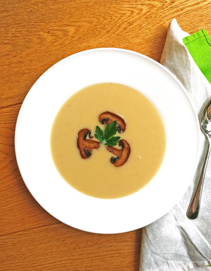 Creamy cauliflower soup with mushroom and parsley decoration, a spoon and green and white napkins, on a brown wooden table
