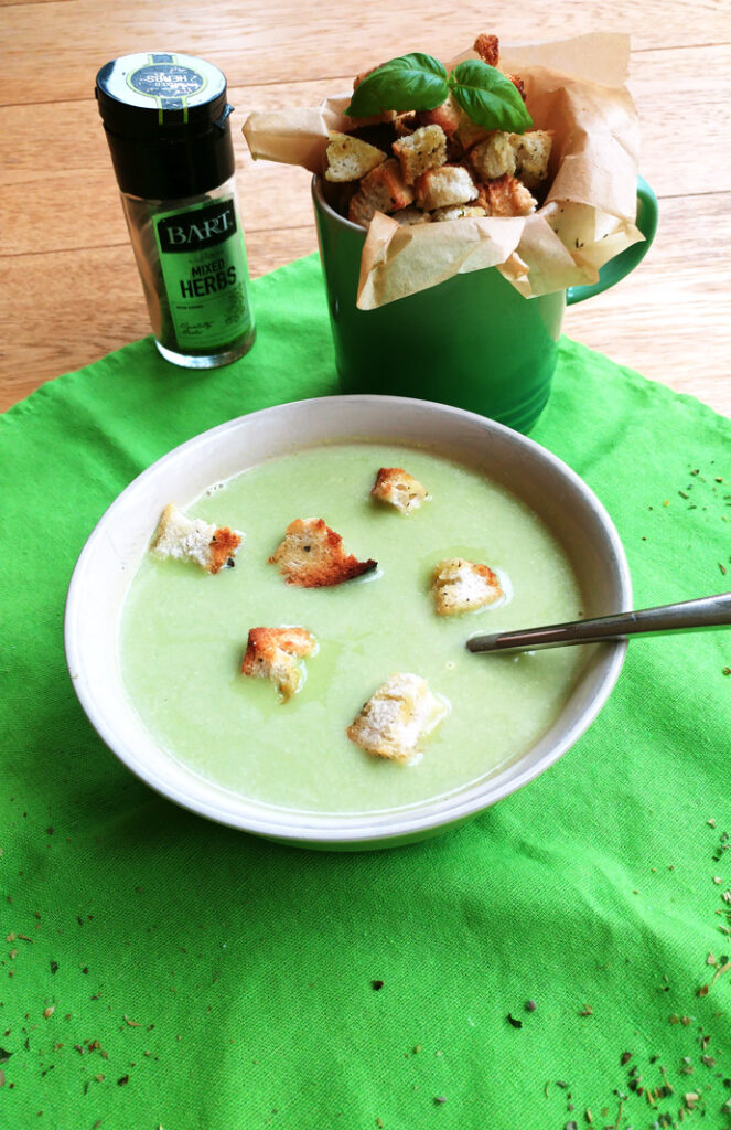Green pea soup with croutons and a spoon on a green napkin, mug with croutons and herbs in the background.