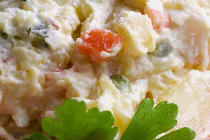detail of potato salad with carrots, gherkins and garden peas, decorated with flat leaf parsley.