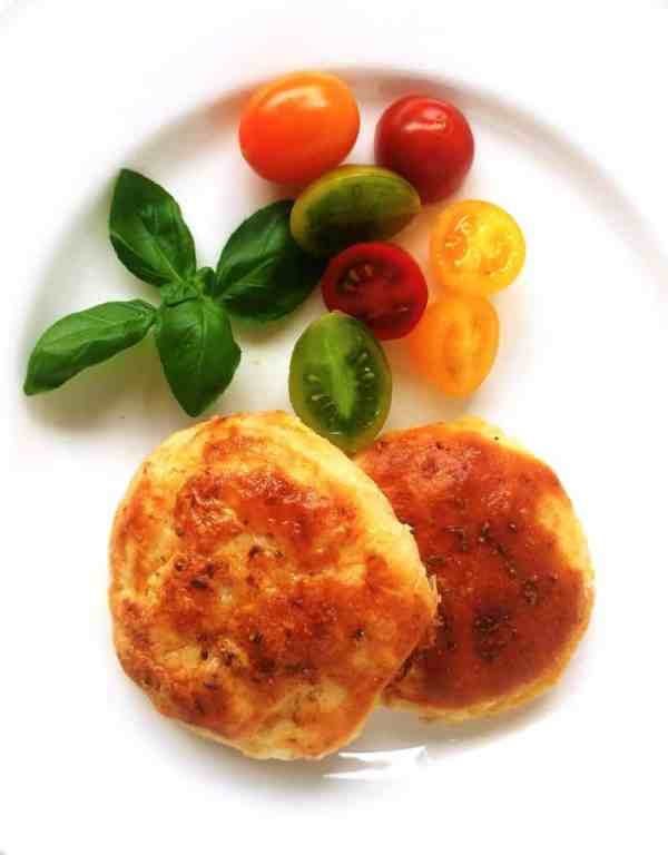 Two savoury potato cakes on a white plate with yellow, red and green cherry tomatoes and basil leaves