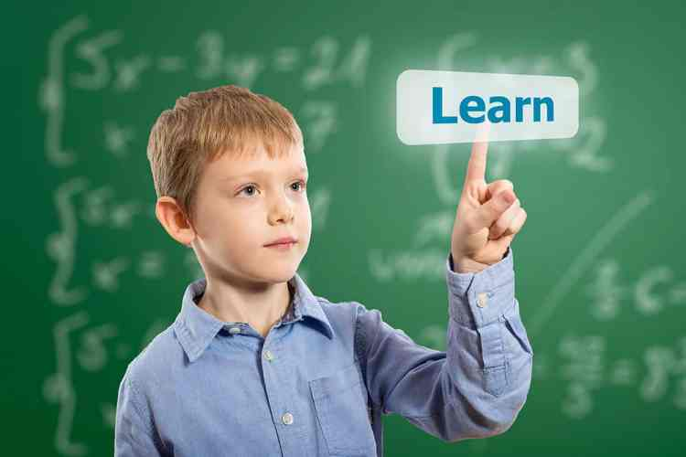"""boy pointing to a chalk board with the word, """"learn"""""""