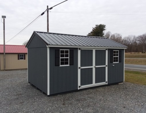10 x 16 size painted a-roof style shed with dark gray siding, white trim, black metal roof, black shutters, ggs 6 foot doors, two windows.