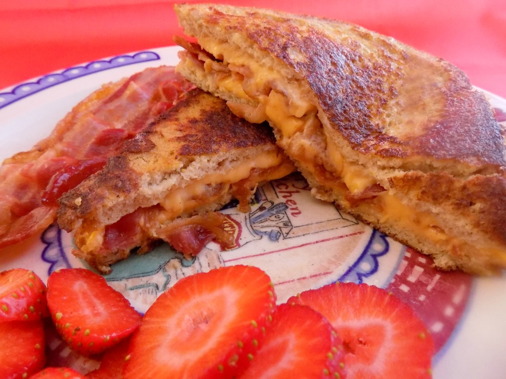 Bacon and Cheese Stuffed French Toast ready to eat with sliced strawberries on the side