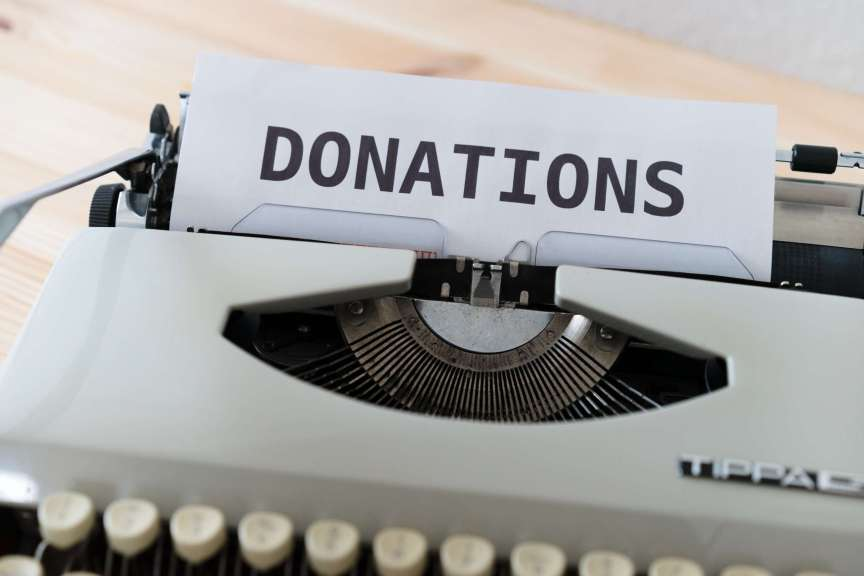 """typewriter with """"donations"""" typed on blank sheet of paper"""