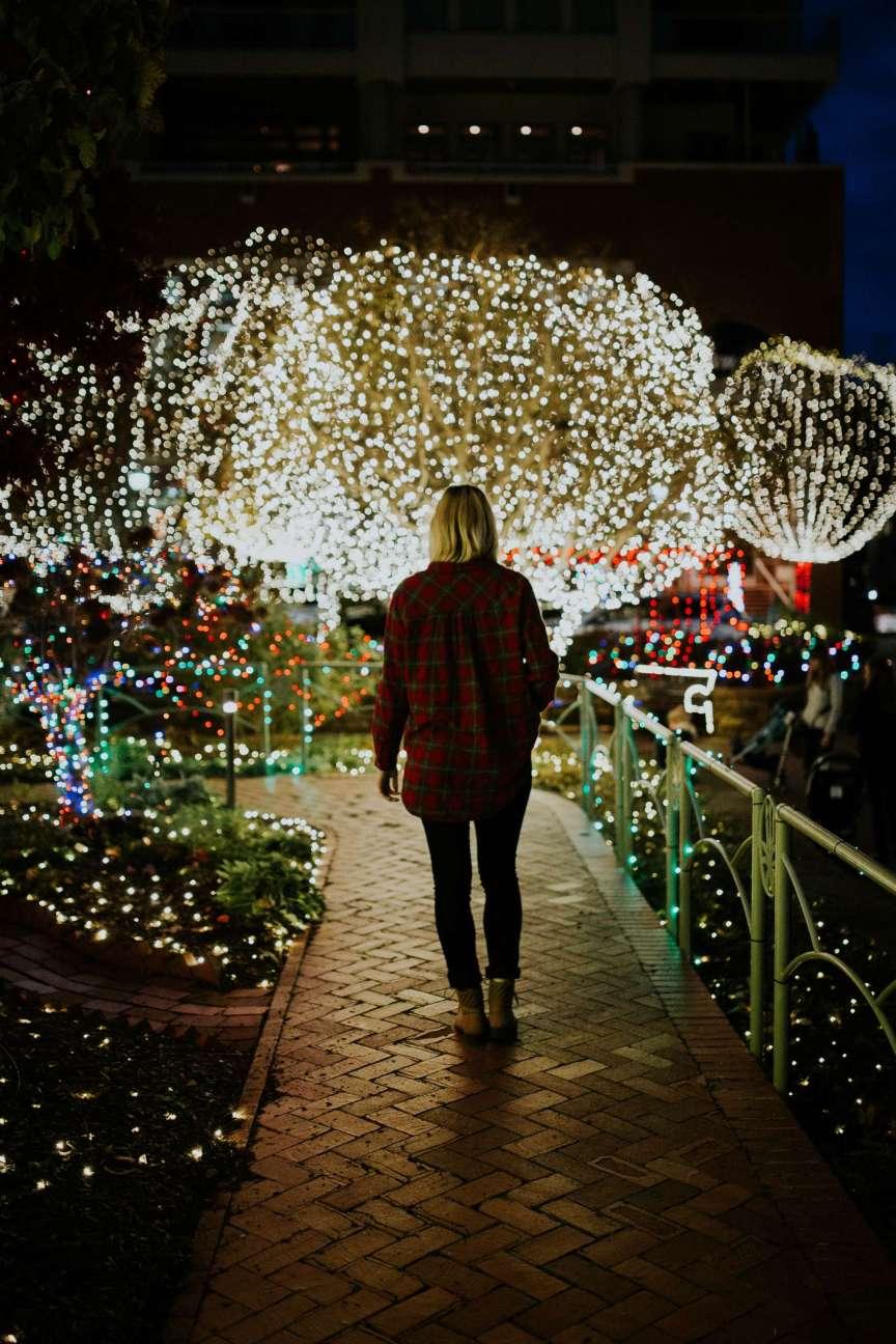 woman walking through holiday light display at nighttime