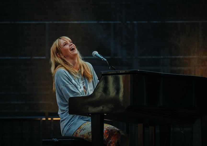 blonde haired woman singing while playing piano