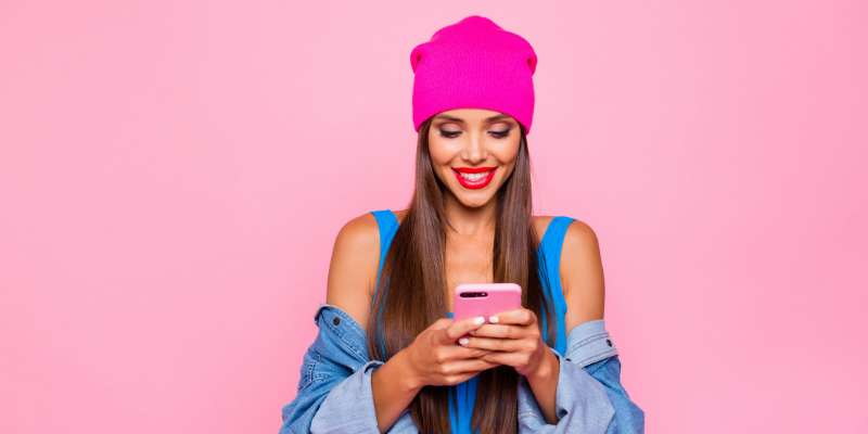 woman with bright pink hat checking phone on a light pink background