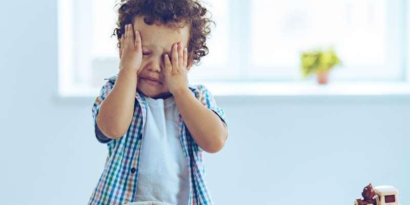 toddler with face in hands upset