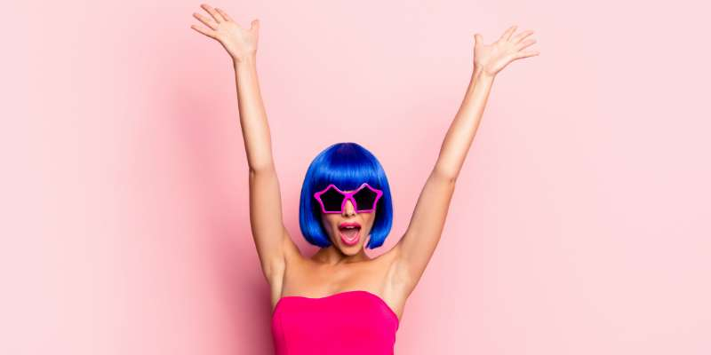 woman with blue wig and star sunglasses wearing bright pink dress in front of a light pink background