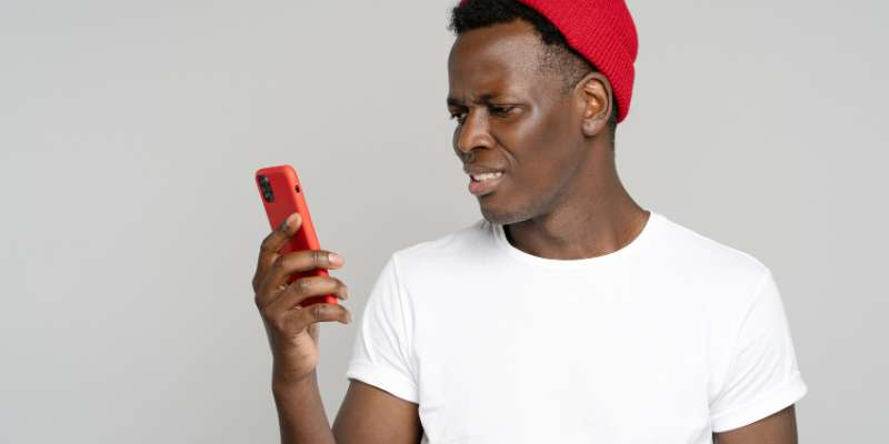 unhappy man in red hat looking at (red) phone with digust