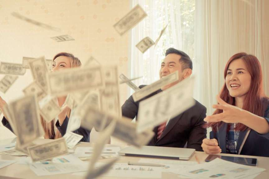 team sitting around conference table throwing money in the air