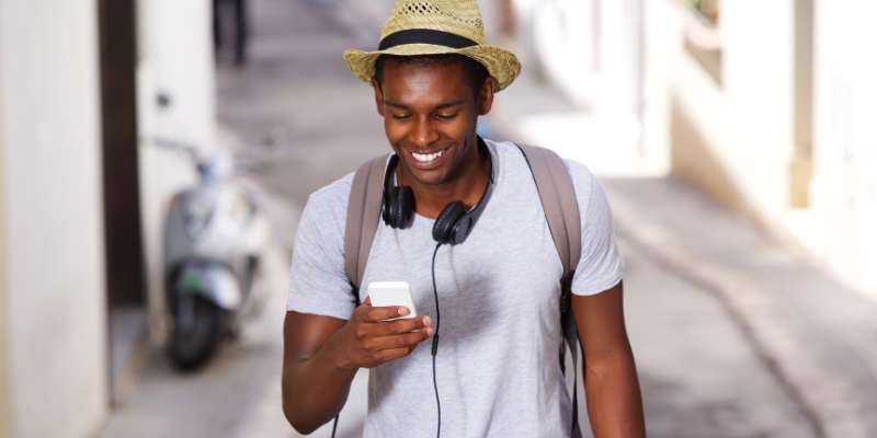 happy guy wearing hat using cell phone
