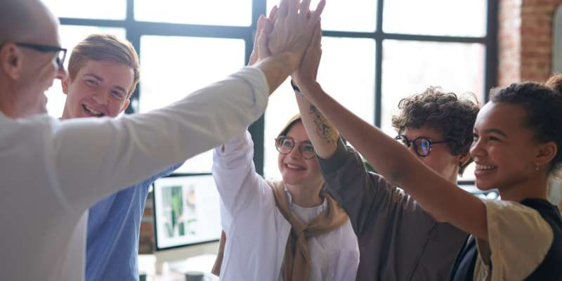 team of people group high-fiving in conference room