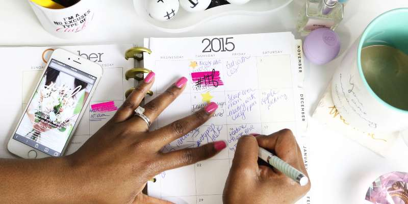 planner with calendar; hands with painted nails writing