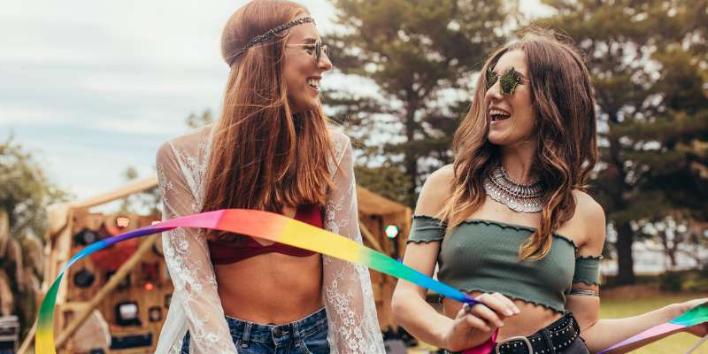 two female friends playing with rainbow ribbon at festival