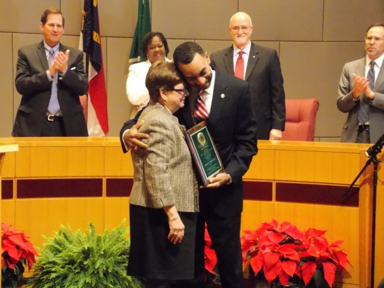 Patsy Kinsey presents outgoing City Councilmember James Mitchell with the Harvey B. Gantt Award on the last night of his service on Council in December 2013.