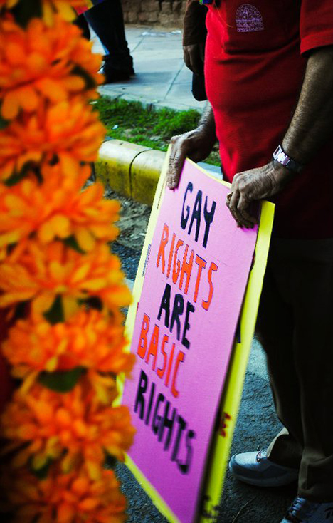 A man holds a protest sign at an LGBT Pride event in New Delhi  in 2010. Photo Credit: Noopur28, via Wikipedia. Licensed CC.