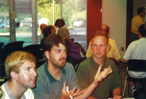 Longtime community leader and early center board member David Lari, left, and other unidentified individuals discuss ideas in this undated photograph from a community center planning meeting.