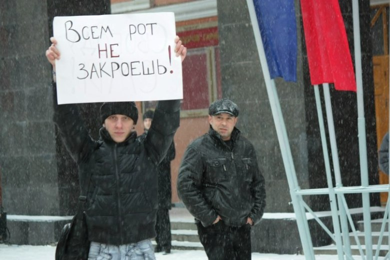 """Andrew Nasonov at a Voronezh demonstration against harassment of the media. His sign reads, """"All mouths are not closed."""""""